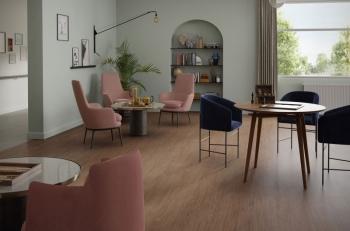 Serene Oak im Gemeinschaftsraum eines Altenpflegeheims: Der Boden aus der Kollektion Acczent Excellence 80 sorgt für Wohlbefinden und verfügt über visuelle Kontraste, die von den Patienten als angenehm empfunden werden.